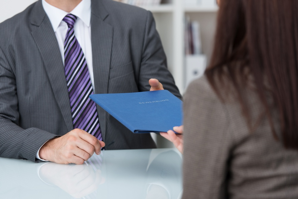 Employment interview with a close up view of a female applicant handing over a file containing her curriculum vitae to the businessman conducting the interview.jpeg